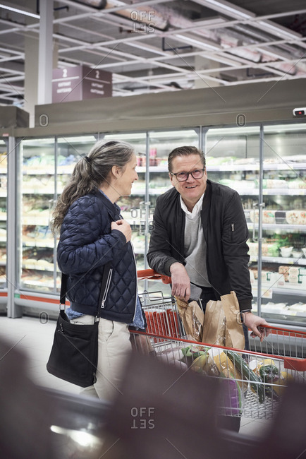 Smiling couple standing with shopping cart at refrigerated section in supermarket