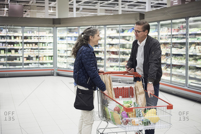 Mature couple talking by shopping cart at refrigerated section in supermarket
