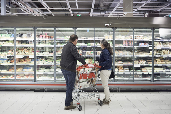 Mature couple looking at food on display at refrigerated section in supermarket