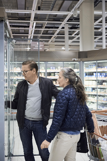 Mature couple standing by shopping cart at refrigerated section in supermarket
