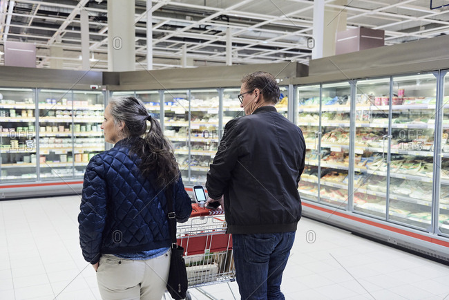 Rear view of couple pushing shopping cart in refrigerated section at supermarket