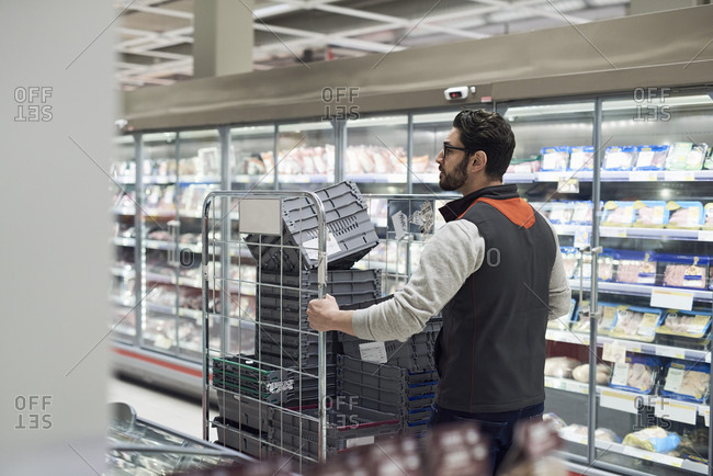 Rear view of sales clerk pushing cart with plastic crates at supermarket