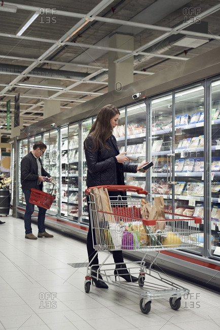 Man and woman buying food from refrigerated section at supermarket
