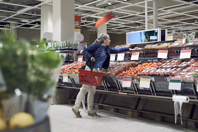 Woman buying vegetables from supermarket