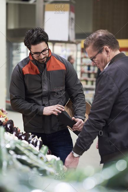 Sales clerk assisting mature man in buying vegetables at supermarket