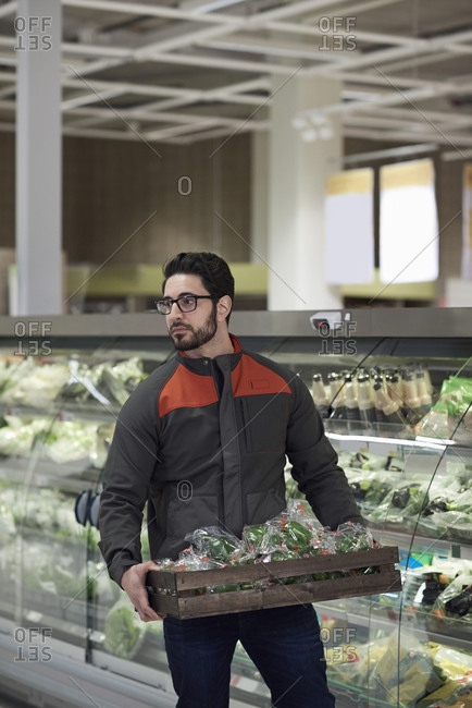 Sales clerk holding crate with green bell peppers by display cabinet while looking away at supermarket