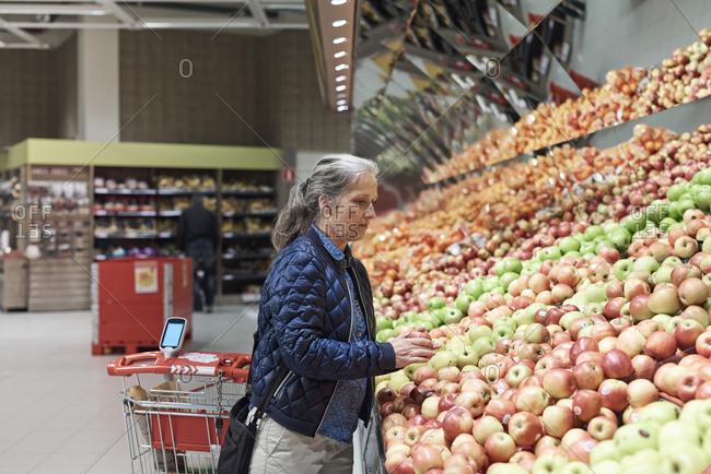 Mature woman buying apples at supermarket