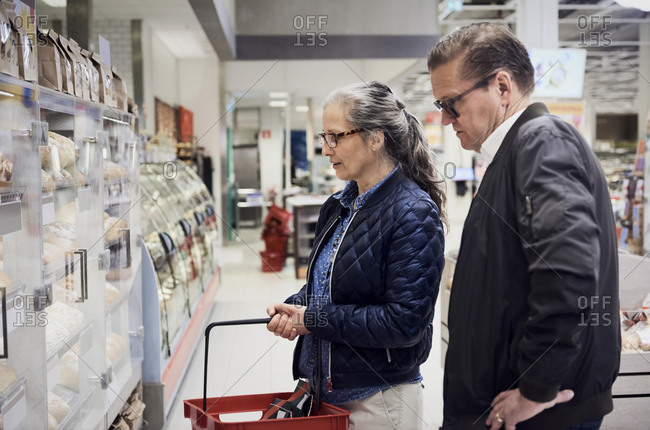 Mature couple looking at food cabinet in supermarket