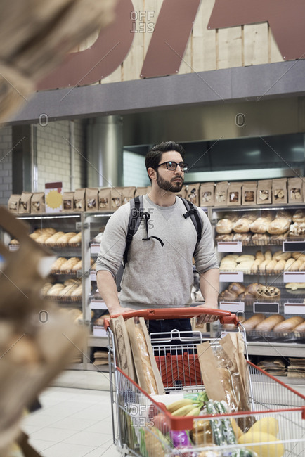 Man pushing shopping cart with groceries against rack at supermarket