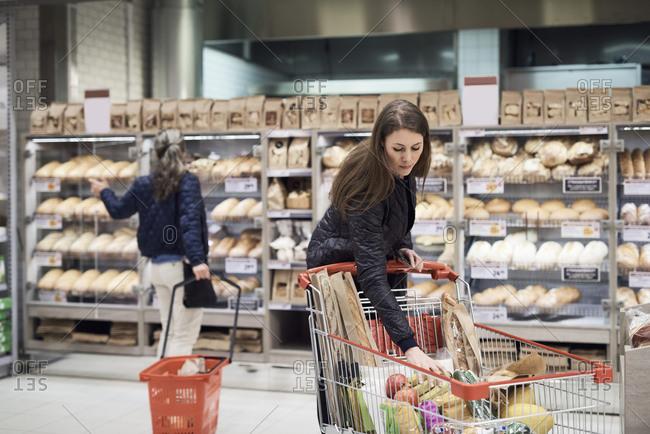 Woman keeping bananas in shopping cart against rack at supermarket