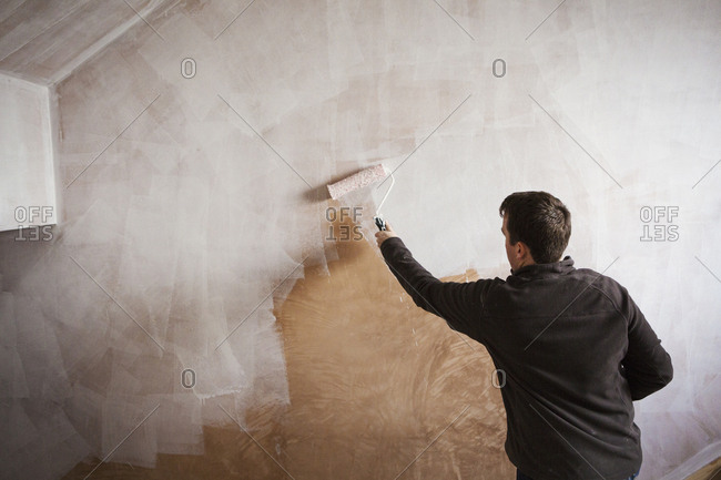 A builder, a painter holding a paint roll, painting a wall with white paint