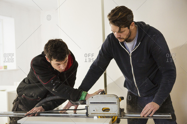 Two builders, cutting plasterboard with a circular saw