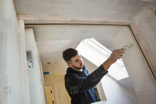 A builder, painter holding a paint brush, painting a door frame
