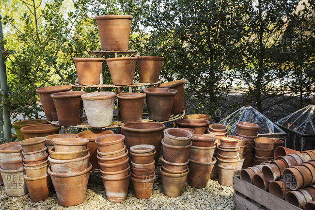 A large stack of terracotta pots in a garden