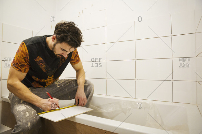 A builder, tiler working in a bathroom, marking a tile with a pencil