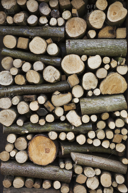 Close up of a stack of wooden logs and twigs, a log store