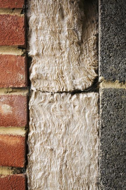 Close up of insulation between a brick and cinder block wall