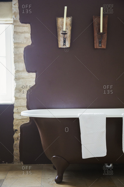 Interior view of a bathroom with freestanding roll top bath with purple painted walls