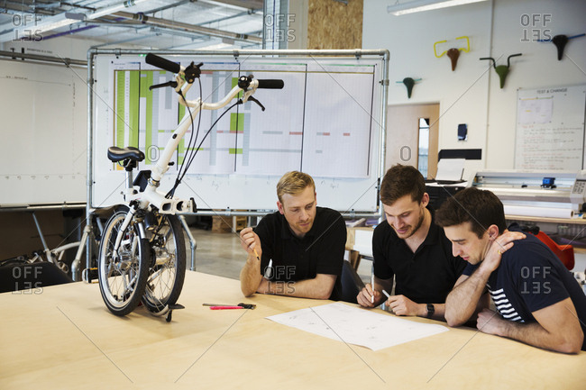 Three men in a meeting at a bicycle factory, sitting at a table with a folding bicycle on the tabletop