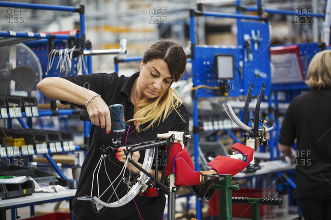 Female skilled factory worker assembling a bicycle in a factory working on the frame and wheels