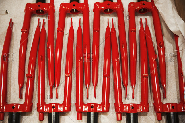 Close up of red metal shapes, red bicycle forks laid out in a pattern