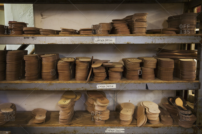 Close up of stacks of leather soles on shelves in a shoemaker's workshop