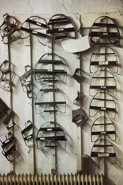 Metal forms, templates for cut leather pieces to make shoes, on a wall in a shoemaker's workshop