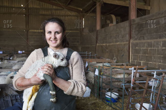 Smiling woman standing in a stable, holding a newborn lamb with bandaged front legs
