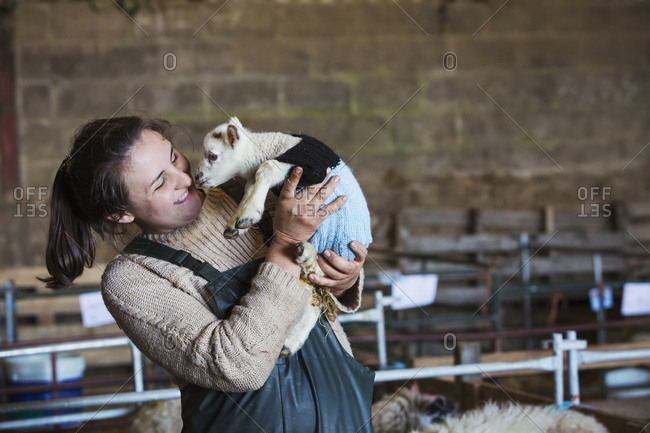 Woman standing in a barn, holding a newborn lamb dressed in a knitted jumper