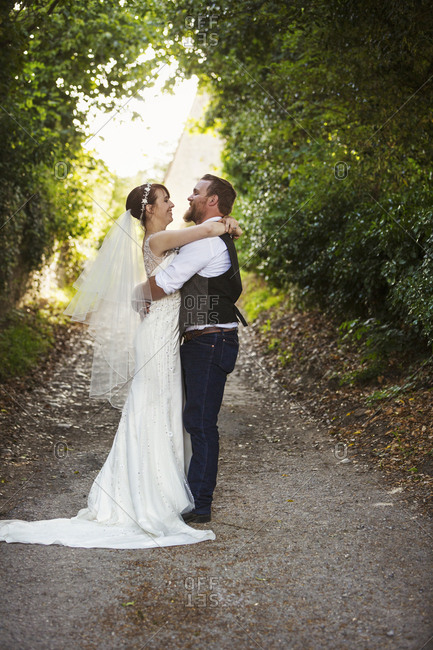 Newlyweds standing outdoors underneath trees, hugging and looking at each other