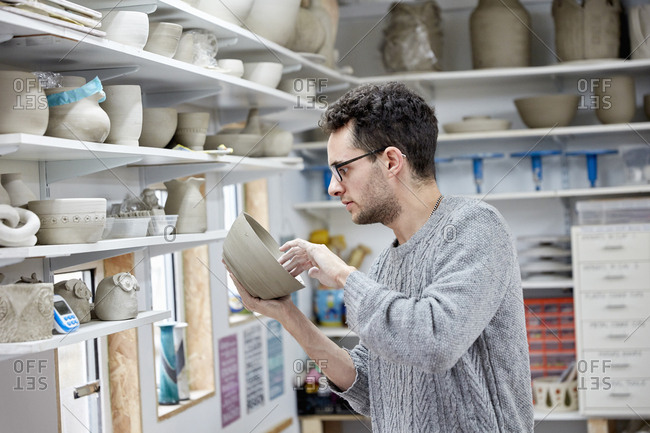 A man inspecting a clay pot, before firing Shelves in a pottery studio full of pots, work in progress