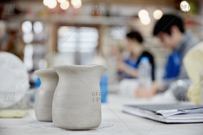 Two clay jugs in the foreground A ceramics class taking place, people seated at a workbench in a pottery studio