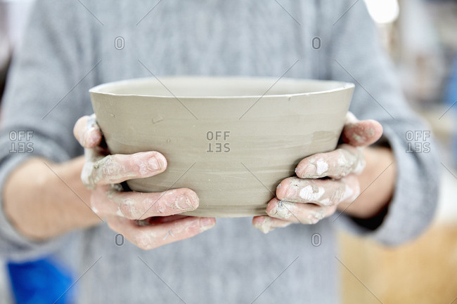 A person holding a freshly thrown clay pot with gently sloping sides