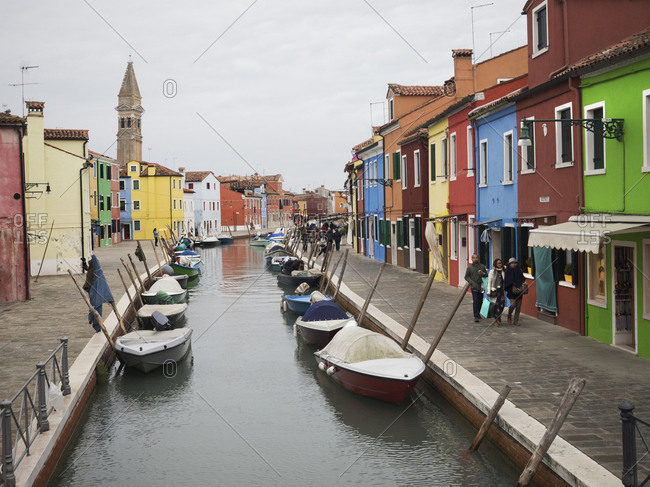 Venice, Italy - June 6, 2017: A narrow canal with boats moored and a terrace of brightly painted house fronts