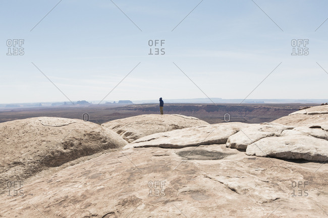 Man standing at overlook at Muley Point, San Juan Canyon in distance, Bears Ears National Monument, Utah