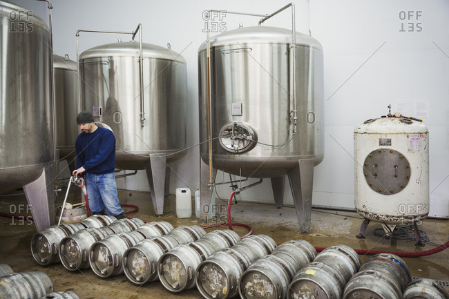 A man filling metal beer kegs from large fermentation tanks in a brewery