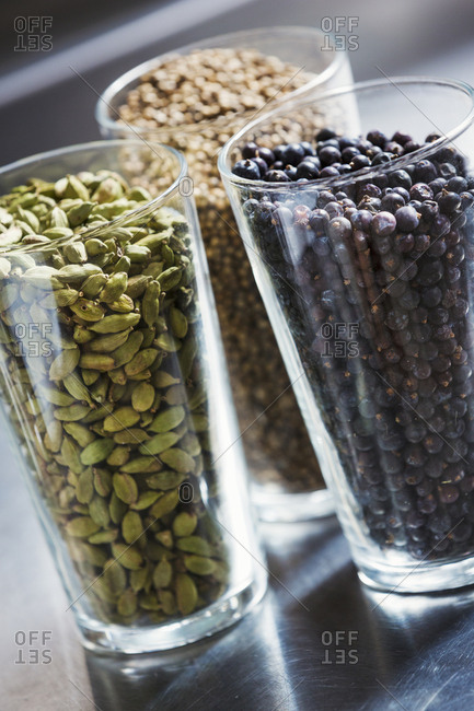 Close up of three glasses with spices, cardamom pods, coriander seeds and juniper berries Flavoring for craft beers