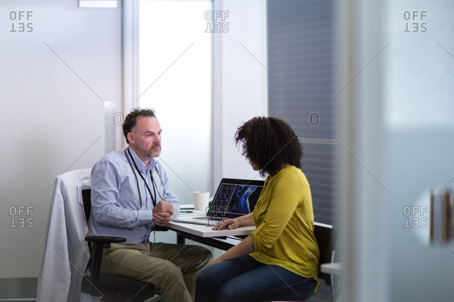 Male Medical Doctor explaining x-ray results to patient