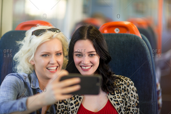 Young adult female friends travelling on train taking selfie