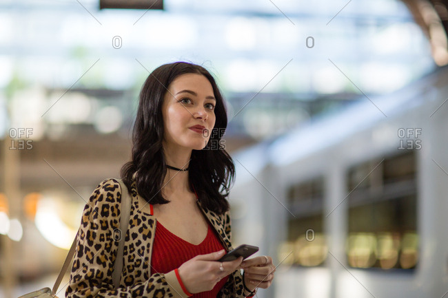 Young adult female on station platform using smartphone