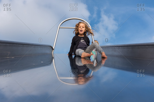 Girl on giant slide, with reflection of the sky