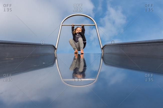 Girl swinging at the top of a giant slide