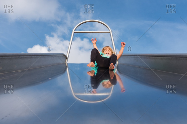 Young child sliding down giant slide