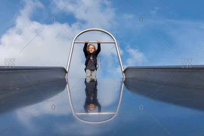 Girl waiting at the top of a giant slide