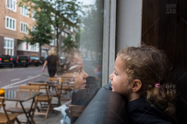 A girl watching looking out the window of a cafe onto the street