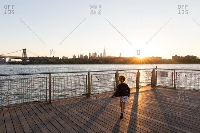 Williamsburg, New York, USA - September 12, 2016: Girl running on Williamsburg pier with a view of Manhattan in the distance