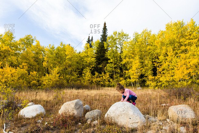 Girl exploring and climbing over rocks in the fall