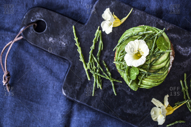 Avocado toast and edible plants on a stone board