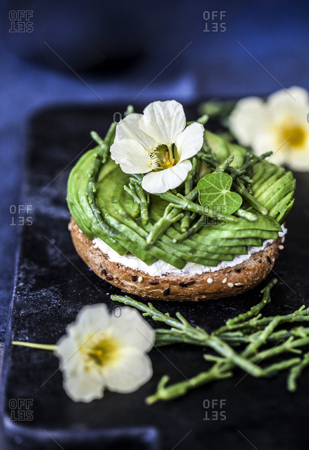 Sliced avocado, cream cheese, and flowers on a piece of bread
