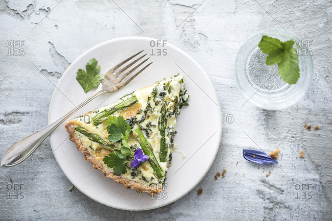 Serving of quiche with asparagus on a white plate